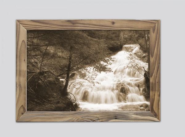 rauschender Wasserfall im Altholzrahmen